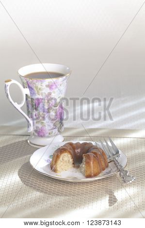 Single mini-bundt cake with brown sugar sauce along with a mug of coffee on a yellow placemat next to a sunny window.