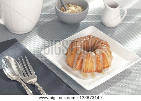Single mini-bundt cake with brown sugar sauce along with a mug of coffee on a blue placemat next to a sunny window.