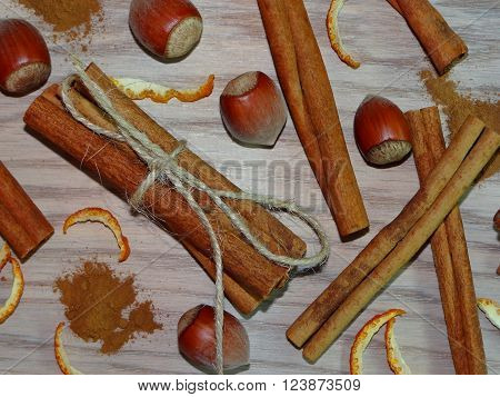 cinnamon sticks tied up with rope and ground cinnamon, which lies on the wooden planks with nuts and orange zest