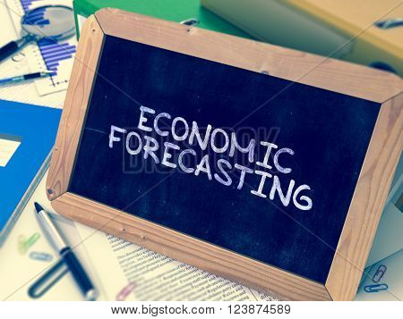 Economic Forecasting Handwritten on Chalkboard. Composition with Small Chalkboard on Background of Table with Ring Binders, Office Supplies, Reports. Blurred Background. Toned Image. 3D Render.