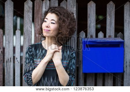 Beautiful asian woman stands near the fence with a mailbox.