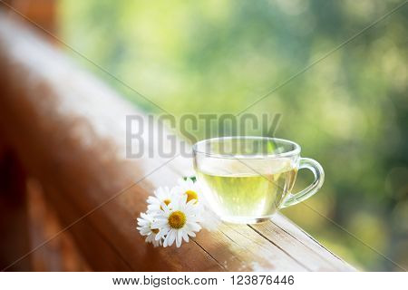 Cup of herbal tea on the railing of the balcony.