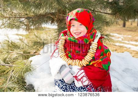 Child girl in Russian pavloposadskie folk scarf on head with floral print and with bunch of bagels on background of snow. Portrait of girl dressed in Russian style
