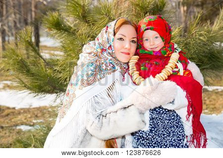 Mother and child girl in Russian pavloposadskie folk scarf on head and with bunch of bagels on background of snow. Russian style