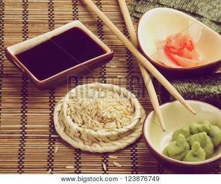 Ingredients to Preparing Sushi with Nori Ginger Wasabi Rice Soy Sauce and Two Chopsticks on Bamboo Straw Mat? Retro Styled