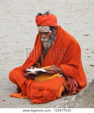ALLAHABAD, UTTAR PRADESH, INDIA - FEBRUARY 13, 2013: Hindu devotee reads and reciting sacred texts during Maha Kumbh Mela festival