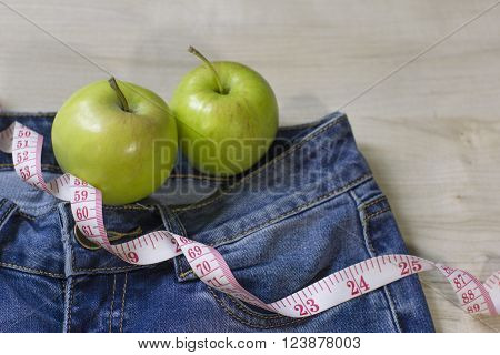 two fresh green apples and blue woman`s jeans and measure tape for weight loss and good body form on wooden background