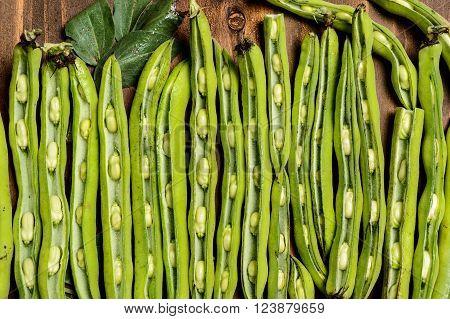 Fresh green beans seen from above on a rough wood floor brown color. Seasonings of Mediterranean cuisine: olive oil, salt.