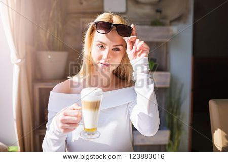 A photo of young, beautiful woman in sunglasses having a glass of cappuccino