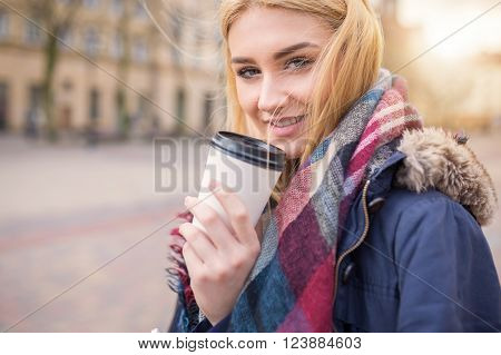 A photo of young beautiful woman at the town square. She's having a cup of coffe and smiling happily.