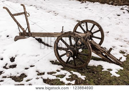 Agricultural old manual plow and wooden wheel.