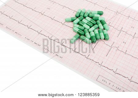Natural green pills on printed EKG sitting on white table