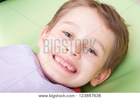 Smiling child with happy face on dentist chair or office. Kid with no fear of dentist concept