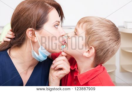 Daring and bold kid kissing dentist woman on the lips