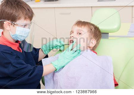 Kids playing in dentist office as doctor and patient using tools and equipment