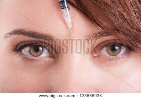 Syringe needle between eyes on forehead. Closeup view.