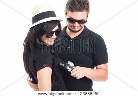 Couple holding an old vintage or retro photo camera feeling disappointed