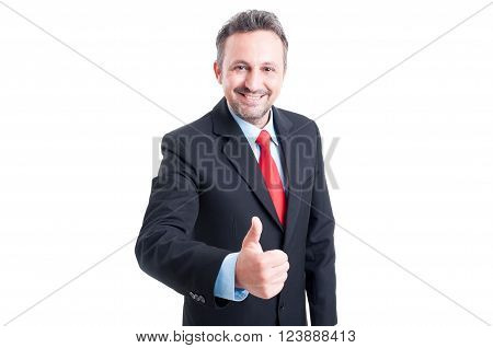 Sales man showing thumb up wearing black suit blue shirt and red tie
