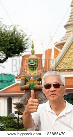 Asian Senior Man With Green Giant In Temple Of Dawn, Bangkok, Thailand Landmark