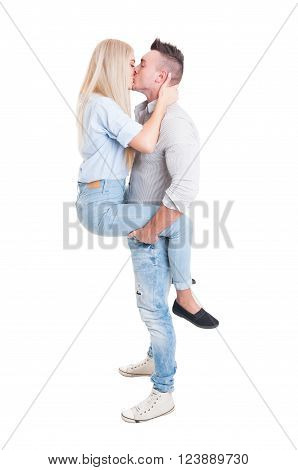 Man holding woman by legs with his strong arms. Full body couple kissing on white background