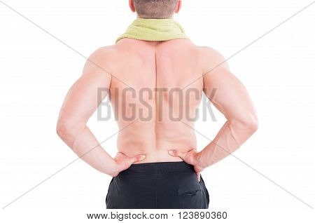 Sportive man holding his lumbar area or lower back after injury and pain