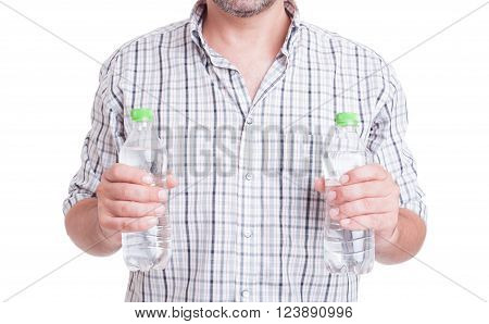 Drink water during summer heat concept with man holding two bottles isolated on white
