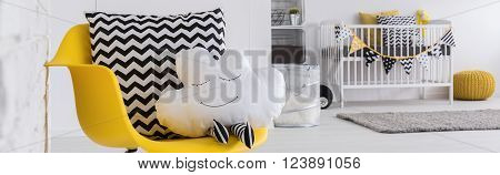 Baby room with yellow chair and decorative pillow cot in the background
