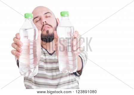 Thirsty man holding two bottles of cold water as hydration or dehydration in summer heat concept