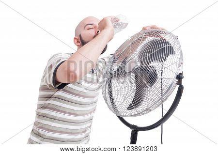Man drinking water near blowing fan as summer heat dehydration concept
