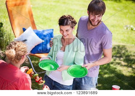 Woman serving meal on afternoon summer garden party