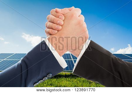 Businessmen handshake as teamwork on solarpower photovoltaic panel background. Renewable energy partnership agreement