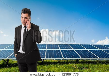Businessman Talking On The Phone On Solar Power Panels Background