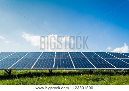 Solar panels on green field and blue sky Renewable sun power concept