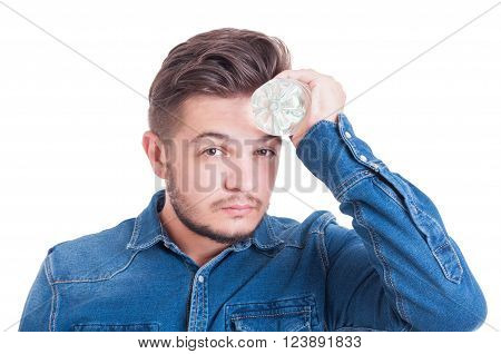 Man cooling his forehead with cold water bottle as summer heat concept