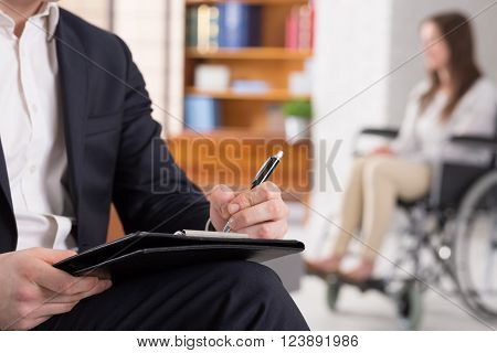 Cropped picture of a psychologist writing down notes and his patient sitting on a wheelchair ** Note: Shallow depth of field