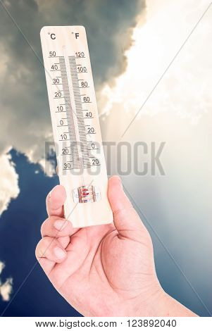 Hand holding thermometer on blue sky background with sunlight and clouds