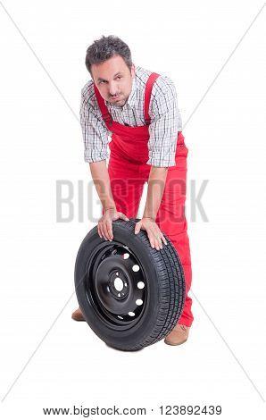 Tired Mechanic Resting On Car Wheel