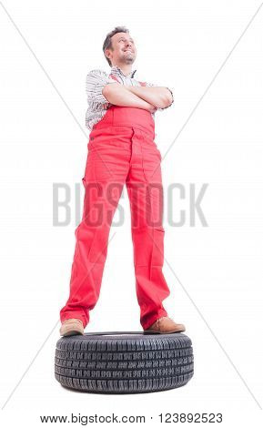 Low Angle Picture Of Mechanic Standing On A Car Wheel