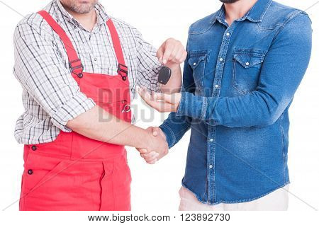 Anonymous Mechanic Handing Car Key To Customer Or Client