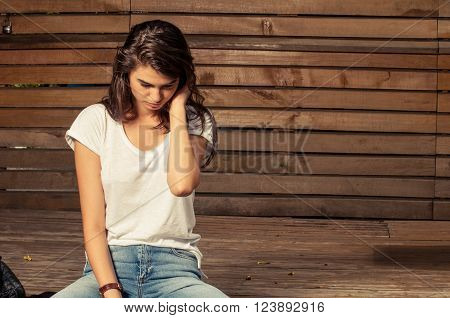 Young and cute female model sitting with head down