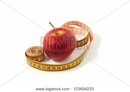 Ripe apple on a white background with measuring tape diet and health.