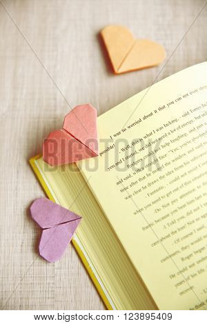 Book and heart shaped bookmark on a light wooden background