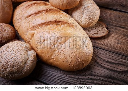 Fresh bread baked goods, harvest on the farm, great food, lots of baked goods, healthy food, a table of old wood, close-up bread, wood grain