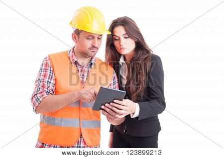Modern builder and business woman using wireless tablet pc as successful partnership and teamwork concept isolated on white background