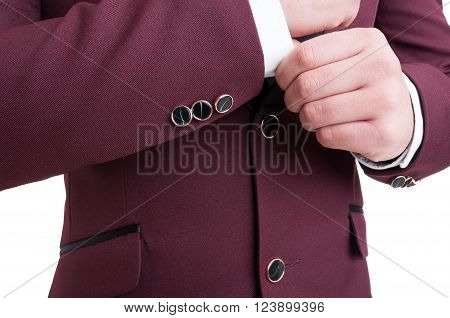 Fashionable male model fixing elegant suit jacket sleeve with buttons. Modern business closeup concept.