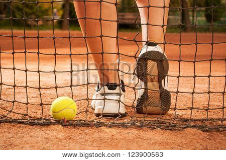 Tennis concept with ball netting and woman feet outdoor on clay court
