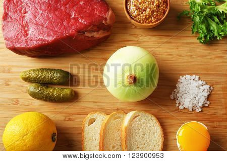 Beef tartare ingredients on wooden cutting board