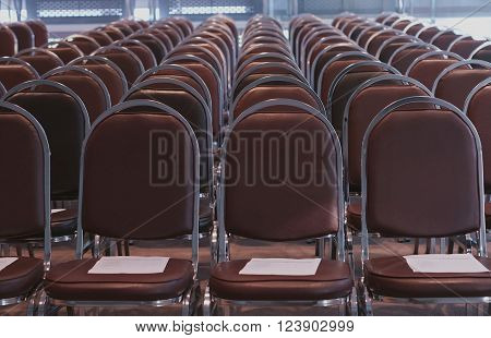Row of brown chairs  was arranged in classroom for conference.