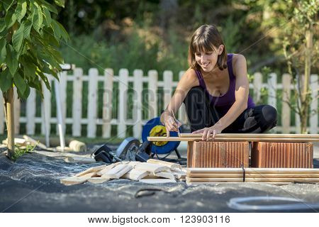 Smiling young woman marking with a pencil where to cut a wooden plank for a backyard fence in a DIY concept.