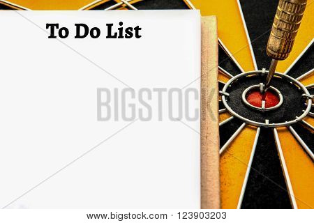 Personal notebook with a to do list and dart target arrow on the center of dartboard To do list and smart goal target success business investment financial strategy concept abstract background